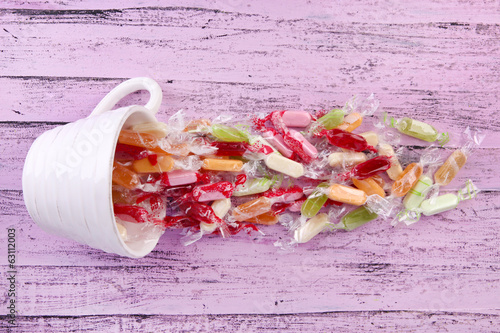 Tasty candies in mug on wooden background