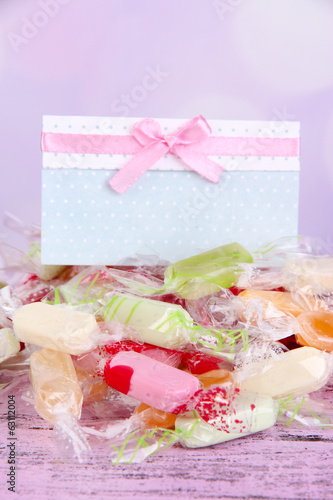 Tasty candies with card on table on bright background