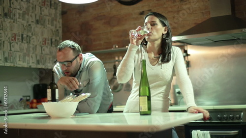 Couple after quarrel drinking wine in the kitchen
