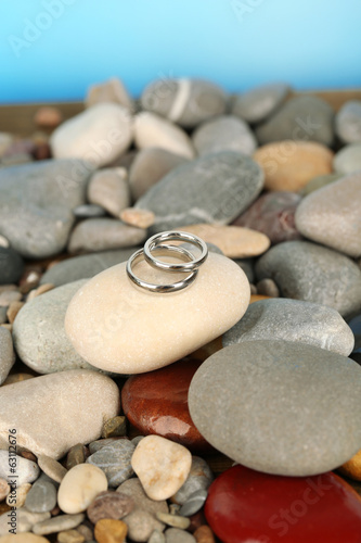 Wedding rings on rocks on blue background