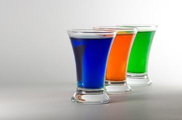 Three multi-colored shot glasses