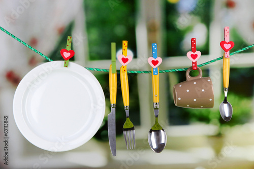 Tableware dried on rope on window background