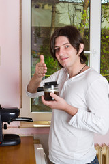 Young man with espresso maker at kitchen