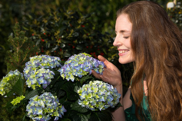 Woman smelling at hydrangea flower in nursery