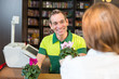 Cashier or shopkeeper in flower shop serving client