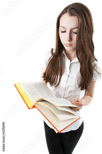 young girl is reading a book while standing
