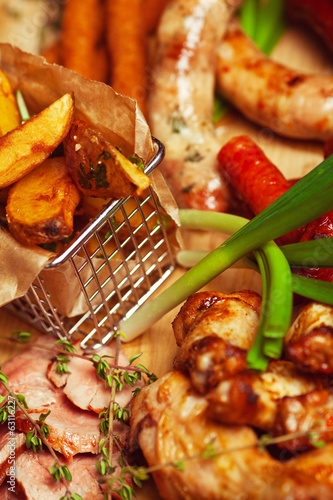 Set of fried meat and small meat sausages served with scallion