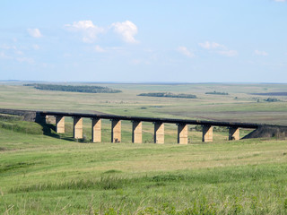 Old viaduct against a blue sky in the steppe