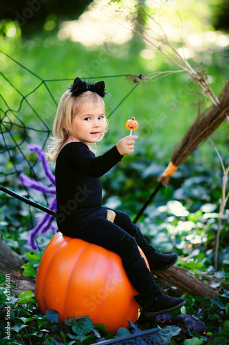 little girl in halloween costume eat candy with jack pumpkin