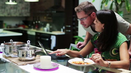 Young woman with laptop eating dinner and calling man