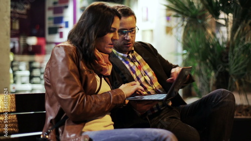 Couple with laptop computer sitting on bench in the night city