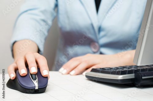 Female hand using computer mouse and keyboard