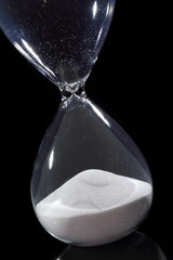 Hourglass isolated on black showing time has run out