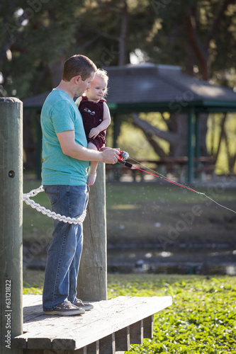 Cute Young Boy and Dad Fishing on the Lake Dock