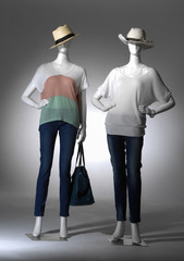 Full length female clothing in hat with bag on two mannequin