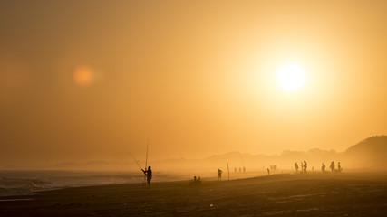 Atardecer en playa de uruguay, personas pescando, hora dorada.