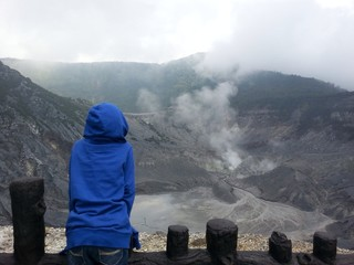 boy watching steam coming out of volcano