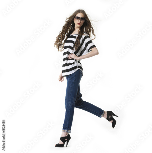 young woman in sunglasses with brown long hairs walking