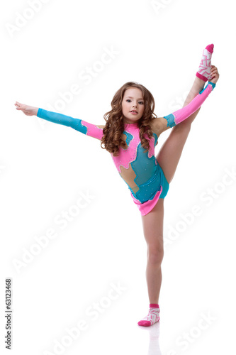 Beautiful little gymnast exercising in studio