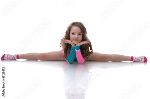 Smiling curly gymnast sitting on splits