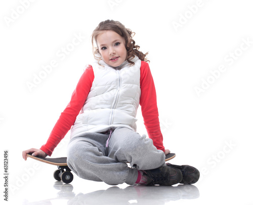Image of cute little girl posing with skateboard