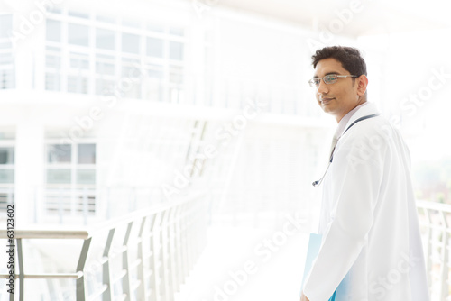 Asian Indian male medical doctor inside hospital.
