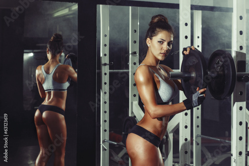 Fototapeta athletic young sexy girl sets weight on barbell in the gym