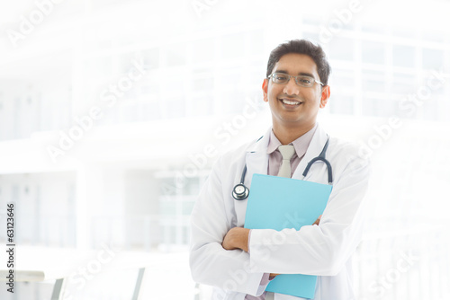 Asian Indian male medical doctor holding file folder