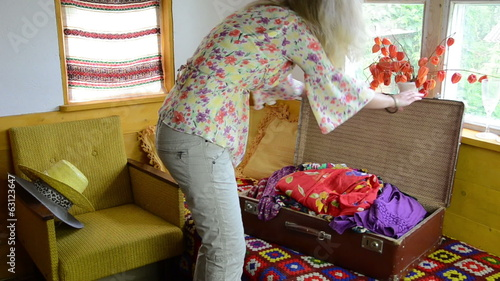 Woman girl fill suitcase portmanteau with summer clothes