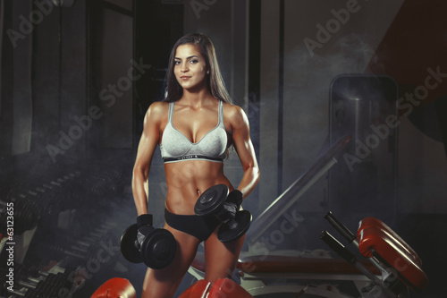 athletic girl doing a fitness workout with dumbbells in the gym - 63123655