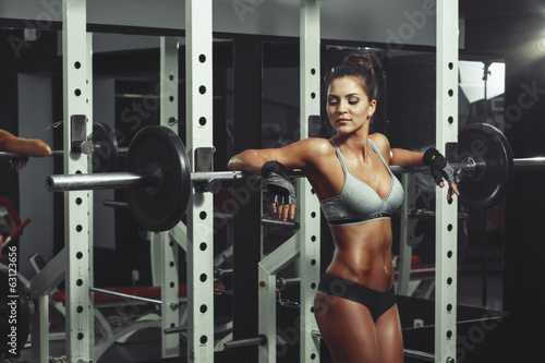 Woman resting after lifting barbell