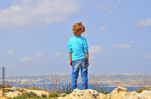 Lonely boy at the cliff edge