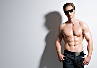 Handsome sexy man in glasses posing at studio.