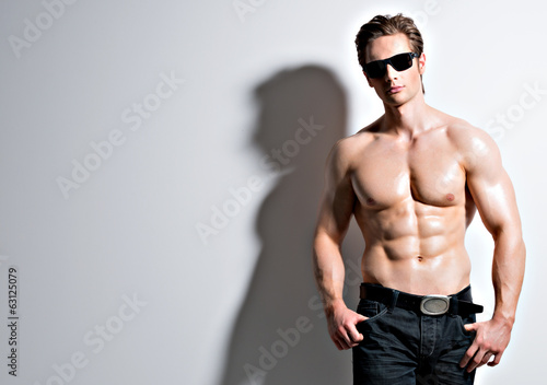 canvas print picture Handsome sexy man in glasses posing at studio.