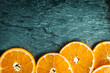 Border of colorful orange slices on slate