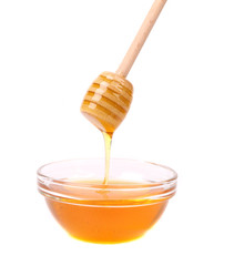 Honey flowing on spoon in a bowl.