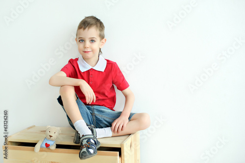 Little boy sitting on the dresser in the red shirt.