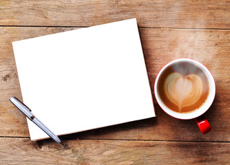 Hot coffee with blank paper note on wood background