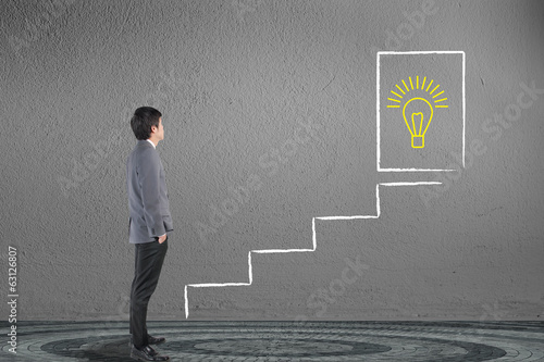 Businessman looking and drawing stairway for solution