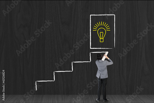 Businessman drawing stairway for success