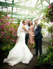 Just married couple posing with friends at greenhouse