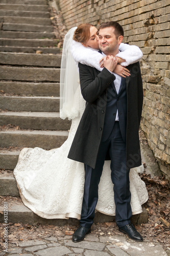 Beautiful bride hugging groom from back on stairs