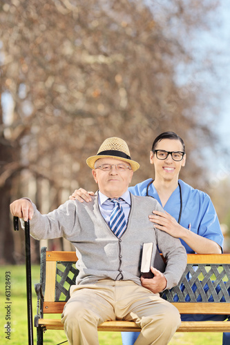 Senior man and a male nurse posing on a bench