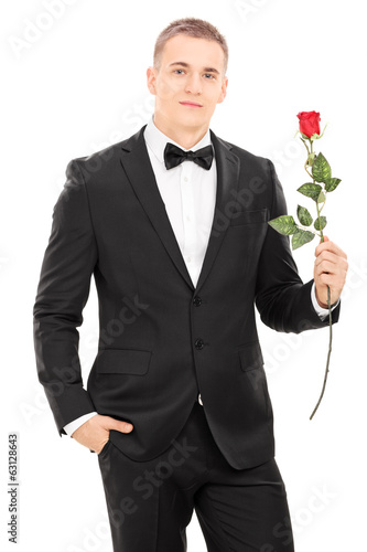 Well dressed man holding a red rose