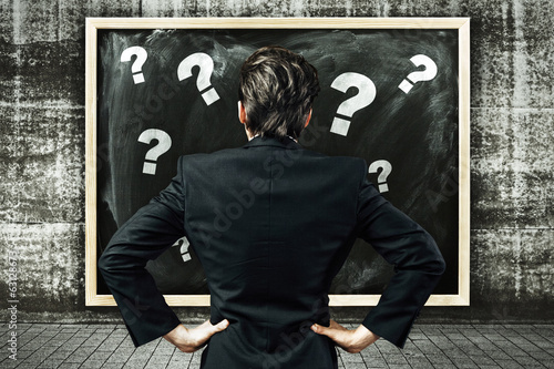 Man looking at a blackboard with question marks