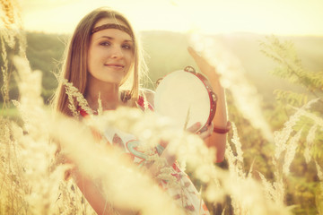 Beautiful young women playing in tambourine in autumn