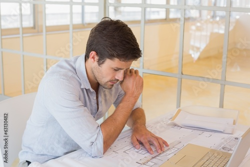 Businessman working on blueprints in office