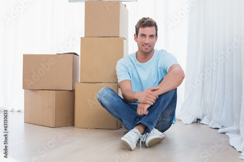 Young man with cardboard boxes in new house