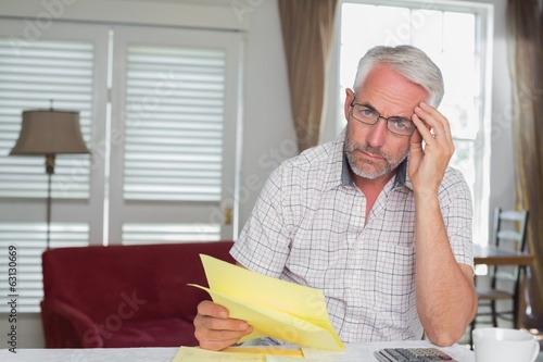 Serious mature man sitting with home bills