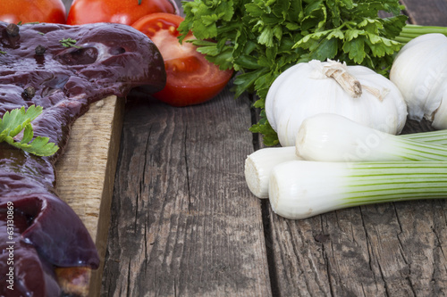 liver with vegetables shot on a wooden background